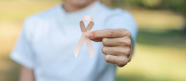 9月の子宮がん啓発月間、生きている人々と病気をサポートするためのピーチリボンを持っている女性の手。ヘルスケアと世界対がんデーのコンセプト