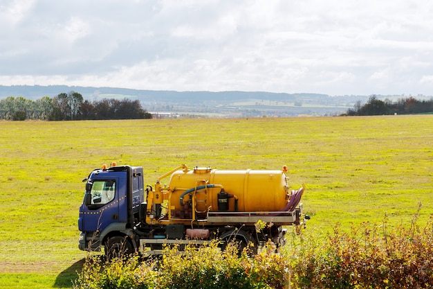 Septic truck on field with grass sewage tank truck sewer pumping machine