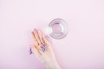 ピンクの背景に水のガラスの近くに人間の手の上にスパンコールと光り輝くカプセル