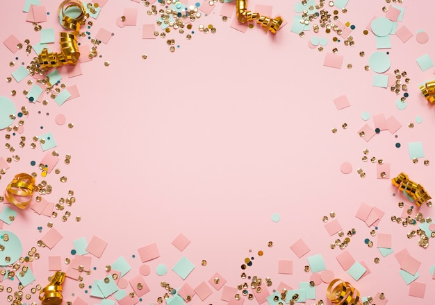 Sequins and confetti frame for copy space pink background