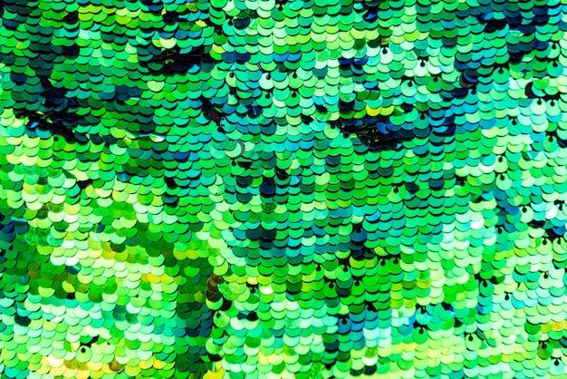 スパンコールグリーンの光沢のある背景、スパンコールパターン。スパンコールのクローズアップでテクスチャスケール。背景を拡大縮小します。光沢のある質感の素材、虹色の生地