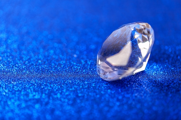 Грандиозный королевский чисто алмаз на голубой сверкная предпосылке sequins, макросе. большой блестящий крупный план