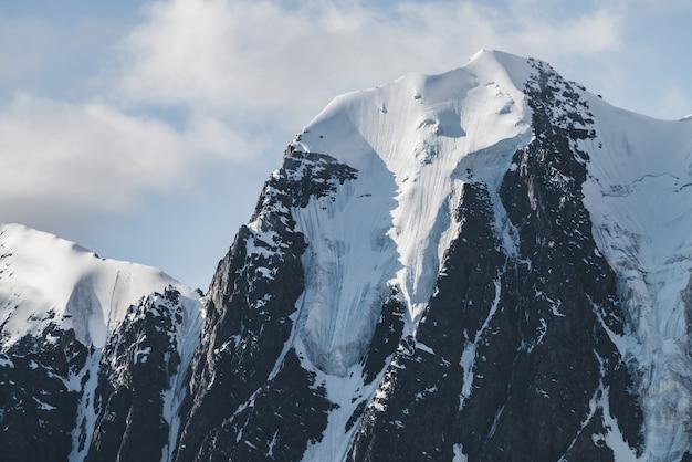 Атмосферный минималистский альпийский пейзаж с массивным свисающим ледником на снежной вершине горы. большой балкон serac на ледниковом краю. облачное небо над заснеженными горами. величественные пейзажи на большой высоте.