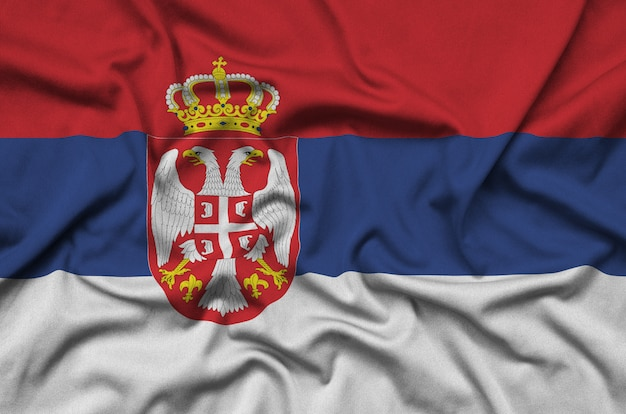 Serbia flag  is depicted on a sports cloth fabric with many folds.