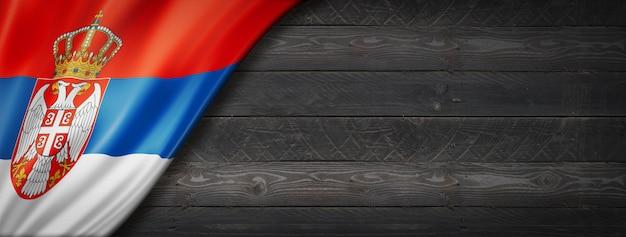 黒い木の壁にセルビアの旗。水平方向のパノラマバナー。