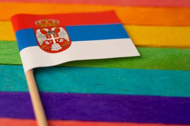 Serbia flag on rainbow background.
