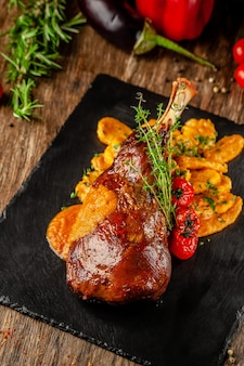 Serbian, balkan cuisine. lamb of leg with gnocchi. serving in a restaurant on a black slate, on wooden table