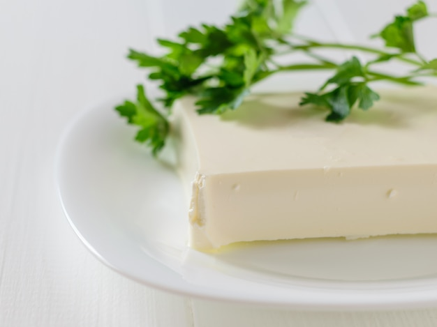 Serbian cheese with parsley leaves on a white table on a white background.