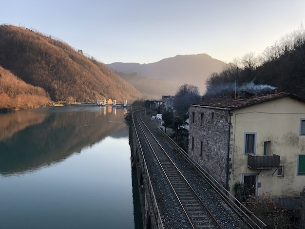 Serchio lake surrounded by railway, buildings and hills covered in forests in italy