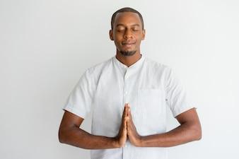 Serene African man touching hands in namaste while meditating.