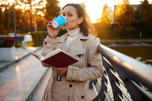 베이지색 아늑한 트렌치 코트를 입은 고요한 아프리카 여성은 테이크아웃 종이컵에서 커피를 마시고, 핸드북을 읽고, 해질녘 호수가 있는 아름다운 가을 공원에서 밖에서 하루를 즐깁니다.