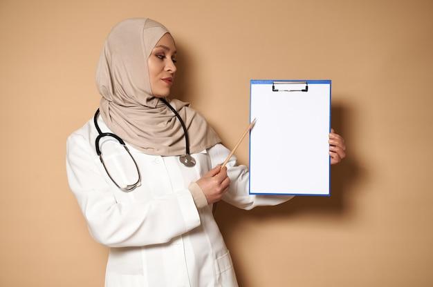 白紙の紙でクリップボードを保持し、それを指しているヒジャーブの穏やかでハンサムな医者。