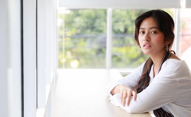 Безмятежная азиатская официантка в униформе сидит за стойкой в кафе и опирается на руку, глядя в камеру.