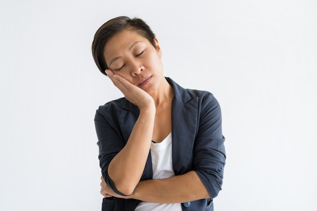 Serene asian woman making sleep gesture with her eyes closed