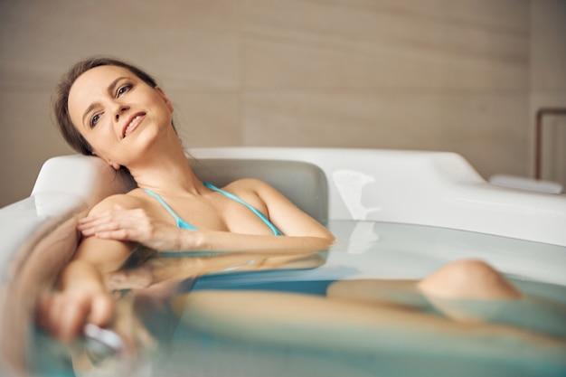 Безмятежная красивая темноволосая современная молодая кавказская женщина в бикини, лежа в горячей ванне