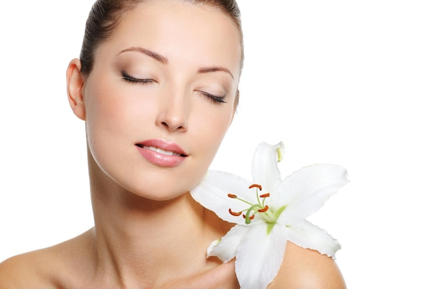 닫힌 눈과 그녀의 어깨에 꽃을 가진 아름다움 신선한 여자의 고요한 얼굴