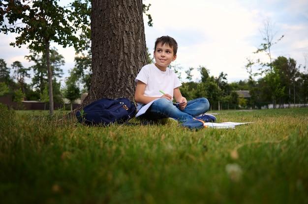 宿題をしている、都市公園の緑の芝生に座って、横を向いて、学校での初日の後の彼のレクリエーションの間に新鮮な空気を楽しんでいる穏やかなハンサムな男子生徒。学校のコンセプトに戻ります。 9月。