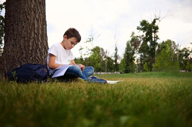 宿題に集中し、都市公園の緑の芝生に座って、学校での初日の後のレクリエーション中に新鮮な空気を楽しんでいる穏やかなハンサムな男子生徒。学校のコンセプトに戻ります。 9月。