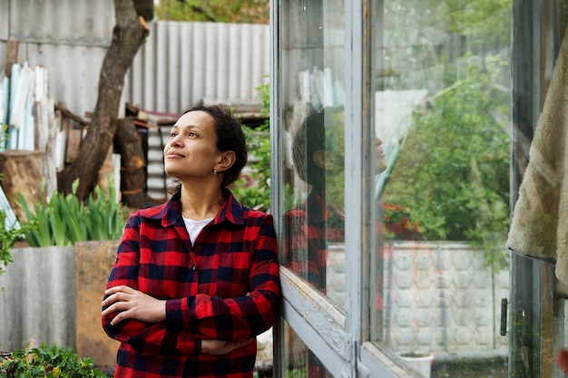 Serene mature woman gardener posing to camera looking away while leaning on a window of an old country greenhouse. hobby, wood, nature, gardening concept