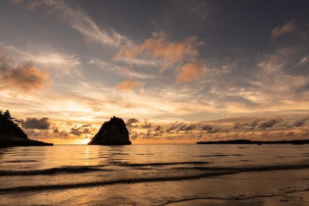 海岸の岩の後ろの海に沈む穏やかなパステル カラーの夕日。西表島。