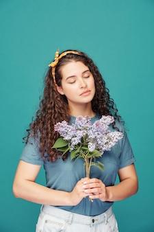 目を閉じて紫色の花を青に保持している巻き毛の穏やかなロマンチックな女の子