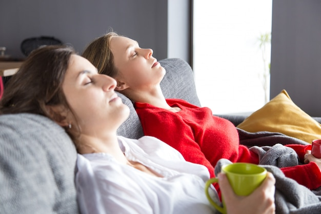 Serene roommates resting on couch over cup of tea