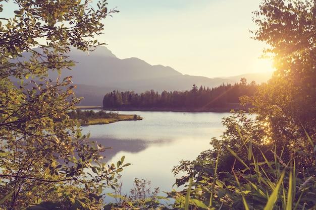 잔잔한 물에 바위가 반사된 캐나다 산 호수의 고요한 장면.