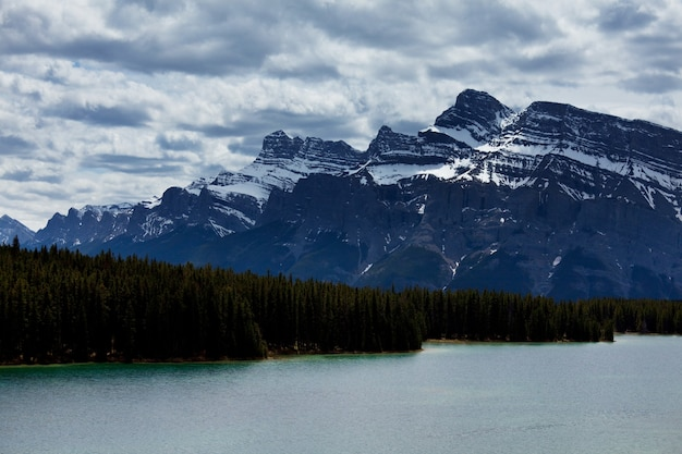 Безмятежная сцена у горного озера в канаде с отражением скал в спокойной воде.