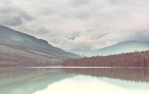 穏やかな海に浮かぶ岩を映し出す山湖の穏やかな景色。