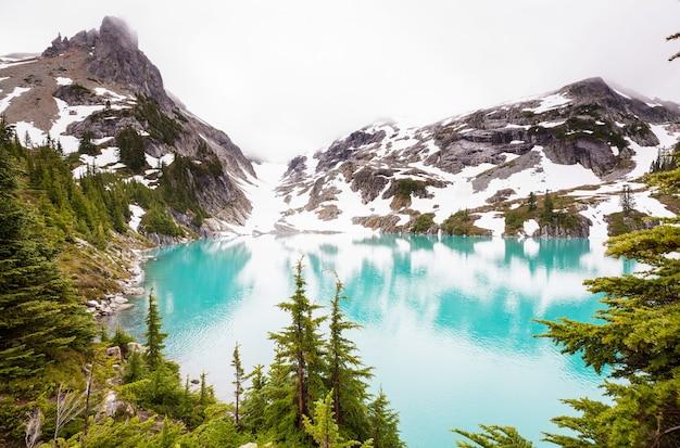 잔잔한 물에서 바위의 반사와 산 호수 옆 고요한 장면.
