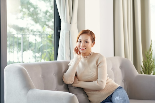 Serene smiling woman resting on couch enjoy air conditioning fresh air at summer day in cosy living room