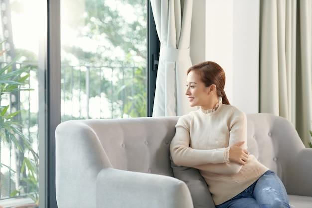 ソファで休んでいる穏やかな笑顔の女性は、居心地の良いリビングルームで夏の日にエアコンの新鮮な空気をお楽しみください