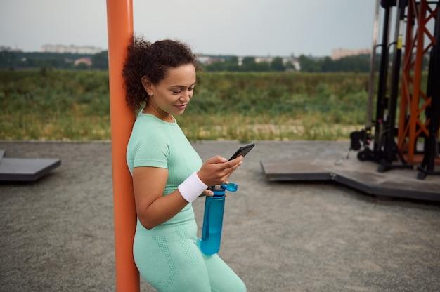 水でボトルを保持し、携帯電話でモバイルアプリケーションをチェックし、クロスバーに寄りかかって、スポーツフィールドでのスポーツ活動の後に休んでいる穏やかなスポーティな美しい若いアフリカ系アメリカ人女性