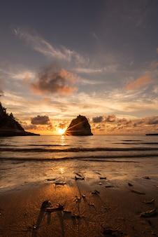 Безмятежный закат с яркими солнечными лучами за прибрежной скалой. блестящий золотистый песок. остров ириомотэ.