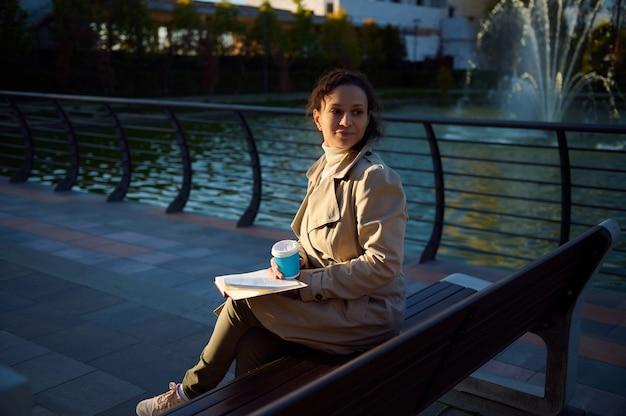 베이지색 트렌치 코트를 입은 고요한 여성은 호수 배경의 공원 벤치에 앉아 재활용 가능한 테이크아웃 종이컵에 커피나 뜨거운 음료를 마시고 책을 읽고 디지털 기기에서 휴식을 즐깁니다.