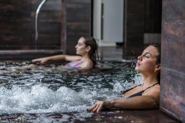 Безмятежная женщина в пузырящейся ванне в спа