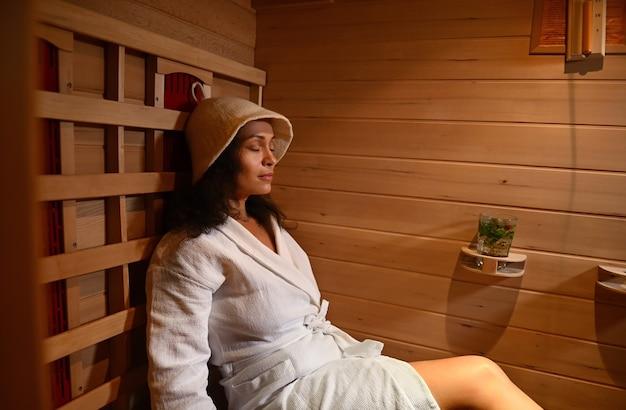 적외선 사우나에서 와플 목욕 가운과 사우나 모자를 쓴 고요한 여성. 스파 트리트먼트, 대체 뷰티 테라피.