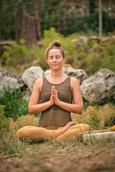 自然の中でパドマサナでヨガを練習している穏やかな女性