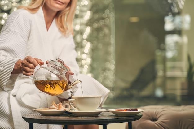 차 한잔에 휴식을 취하는 동안 유리 책상에 앉아 고요한 여자