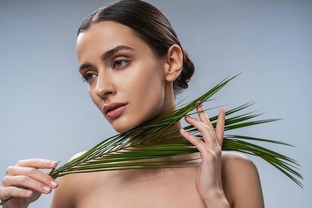 식물 잎을 가진 고요한 젊은 매력적인 여성