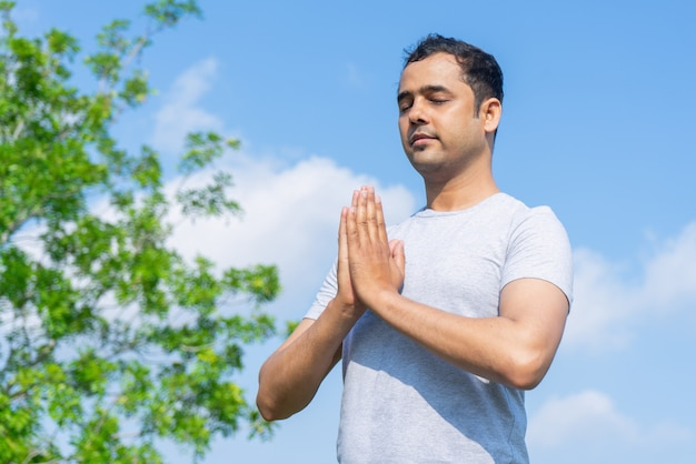 Serene young indian man meditating outdoors with his eyes closed