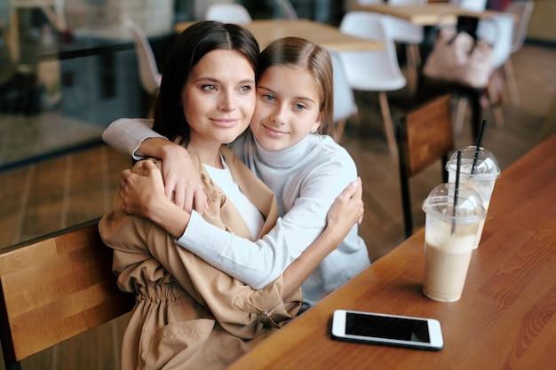 穏やかな若い女性と娘がカフェでリラックスしながらミルクカクテルを飲みながら抱擁に座っています。