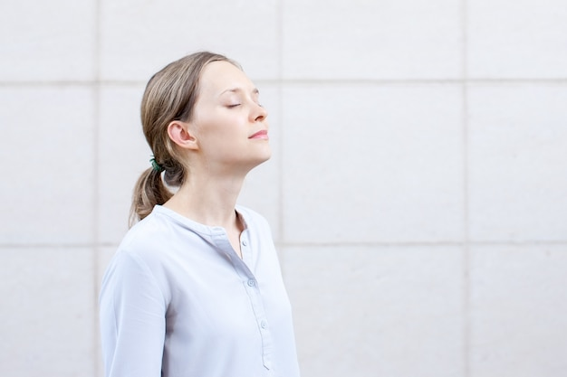 Serene young woman with closed eyes meditating