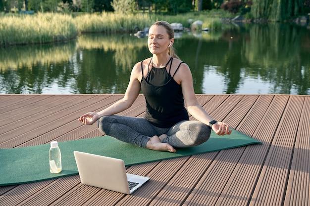 ノートパソコンでチュートリアルを見ながら蓮華座に座って瞑想する静けさのスポーティなリラックスした女性
