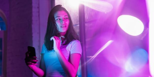 주의를 기울였습니다. 네온 조명이 켜진 실내에서 잘생긴 세련된 여성의 영화적 초상화. 보라색 - 파란색의 영화 효과처럼 톤. 실내에서 화려한 조명으로 스마트폰을 사용하는 백인 모델입니다. 전단.