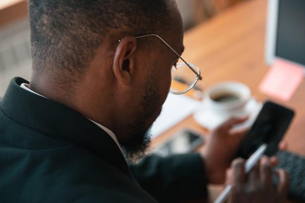 オンラインサーフィン。アフリカ系アメリカ人の起業家、ビジネスマンはオフィスに集中して働いています。クラシックなスーツ、ジャケットを着て、セリオスで忙しいように見えます。仕事、金融、ビジネス、成功、リーダーシップの概念。