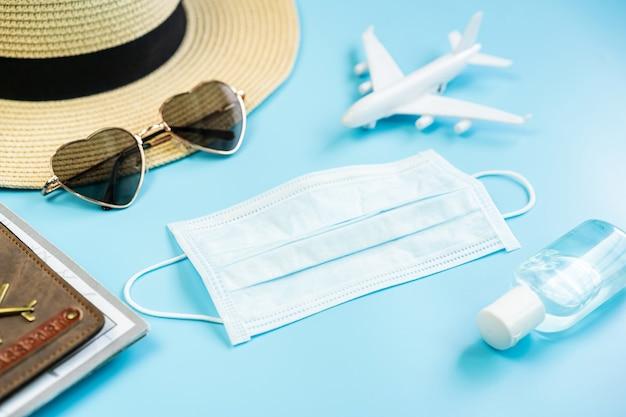 Серьезная маска с предметами для путешествий и паспортом, концепция путешествия во время эпидемии коронавируса