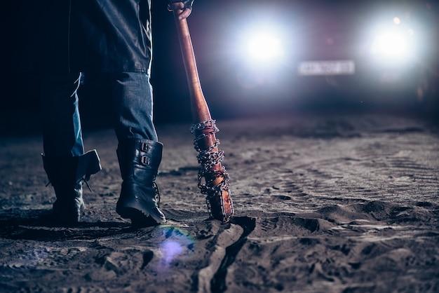 Серийный маньяк рука с кровавым крупным планом бейсбольной битой, автомобильный свет в ночное время. ужас, кровавый убийца
