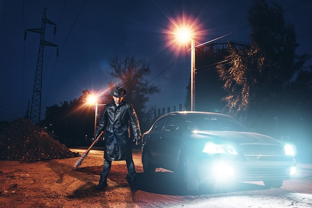 Serial maniac in leather coat and hat with bloody baseball bat wrapped in metal chain against black car with light at the night. horror, bloody murderer, murder weapon