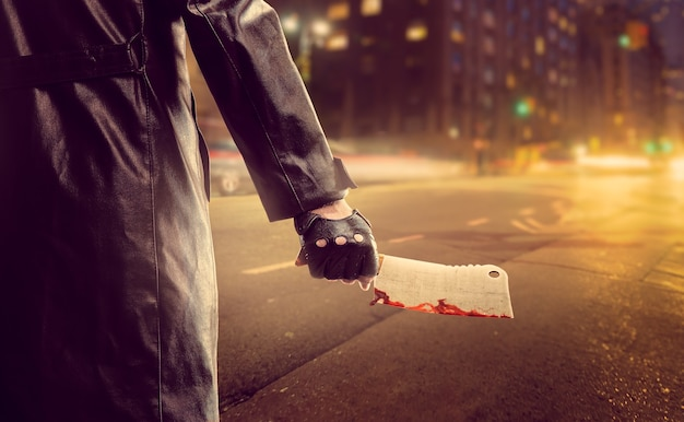 Serial murderer with bloody meat cleaver on road